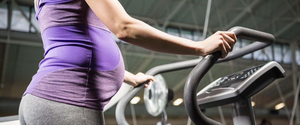 Pregnant woman standing on a fitness machine - Simply Gym